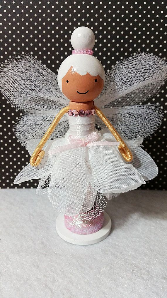 White Fairy Shea, a super cute wooden clothespin doll stands just over four inches tall, and is uniquely hand painted in vibrant colors and wears a white daisy petal dress embellished with sparkling pink rhinestones.