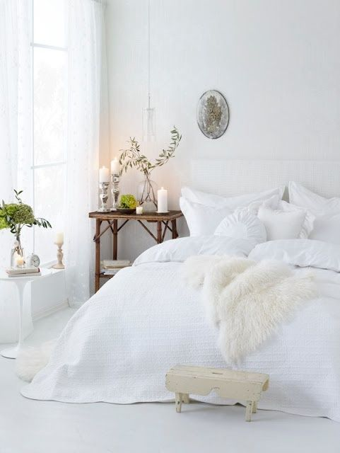 All white bedroom, including a sheepskin. Wooden bedside table is the only contrast, plus a plant.
