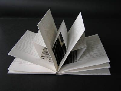 Identity Document by Helen Malone. 2008. Awagami Washi Inkjet paper, Canson paper, inkjet text and prints. The pages reveal partially concealed illustrations and contrasts the revelatory nature of bureaucratic documents with one's hidden real identity and character. Codex book. 14 cm x 10.5 cm.
