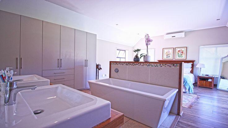 En-suite and open plan bathroom with wood floors.