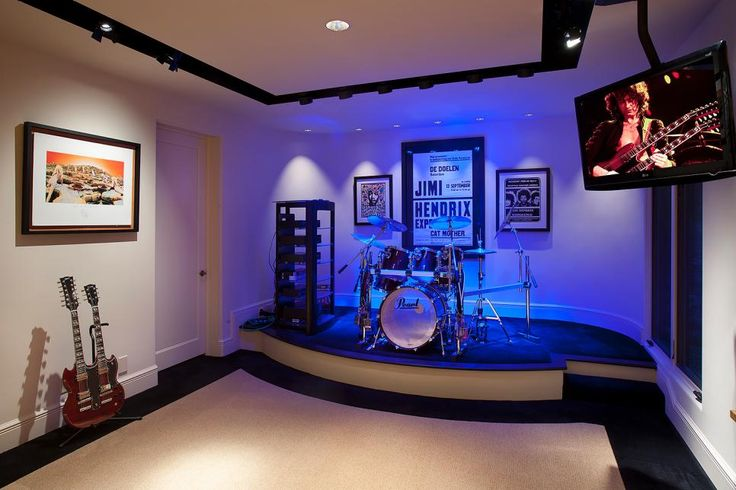 Blue lights illuminate a sleek, contemporary black and white stage where a full drum set sits. Framed concert posters decorate the walls while music videos play on a screen that hangs from the ceiling.