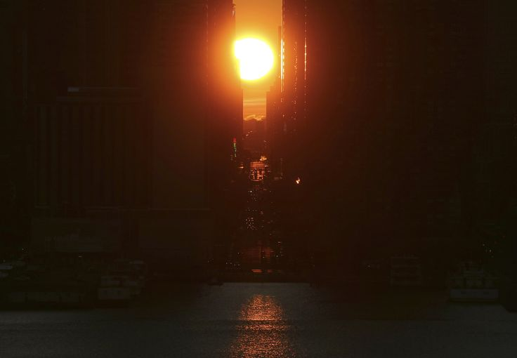 The sun rises above 42nd Street in New York City on November 27, 2016, as seen from Weehawken, New Jersey.