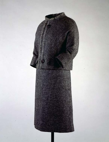 Salt-and-pepper wool tweed suit with fringed neckline and front, by Chez Ninon, 1961. Designed after a spring/summer model by Givenchy. Worn by First Lady Jacqueline Kennedy during her arrival in Ottawa, Canada on May 16, 1961. She also wore it during museum visits with Andre Malraux in Paris, France on June 2, 1961 and during President Kennedy's address to the United Nations in New York City, New York on September 21, 1961.