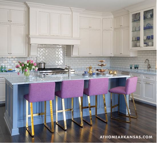 A cornflower blue island picks up on the blue marble countertops in this chic and colorful kitchen by interior designer Andrea Brooks in Arkansas. And the violet bar stools add a touch of whimsy.