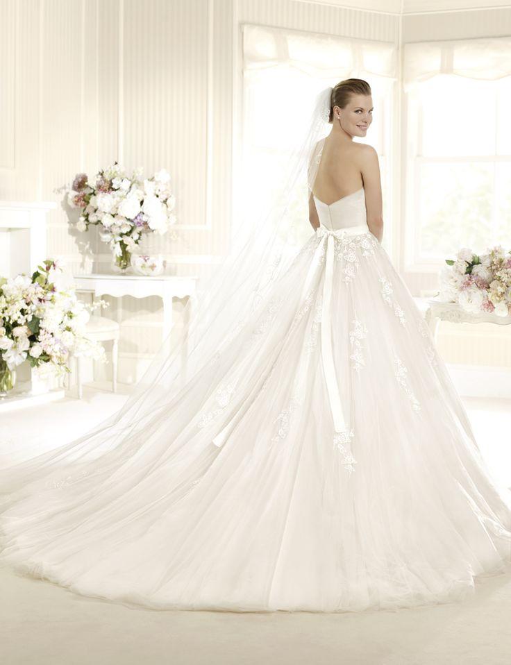 Открытое свадебное платье очаровывает своей пышной юбкой с многослойным объемным шлейфом средней длины. Прямой лиф подчеркивает сдержанные торжественность и элегантность образа.  Декоративными деталями служат широкий пояс на талии и покрывающие лиф и верхнюю часть юбки аппликации из нежного кружева с рисунком, изображающим розы.
