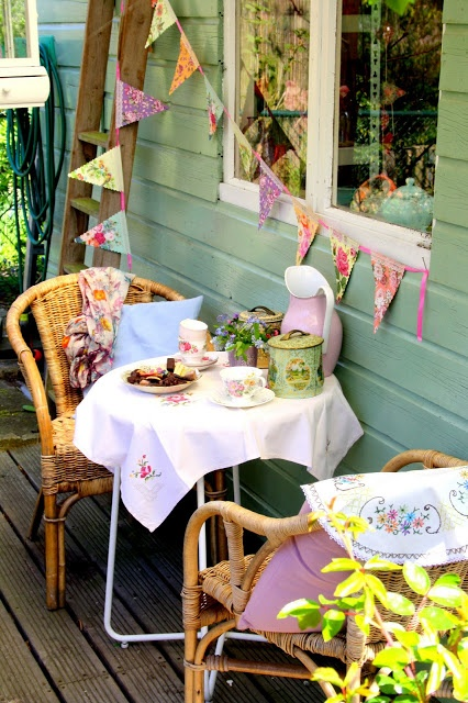 A lovely outdoor setting; tea for two outdoor coziness...wicker, vintage linens and floral fabric pennant banner via http://madeliefje-madelief.blogspot.com/