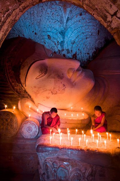 Monks light up the inside of one of the temples at Pagan, Burma