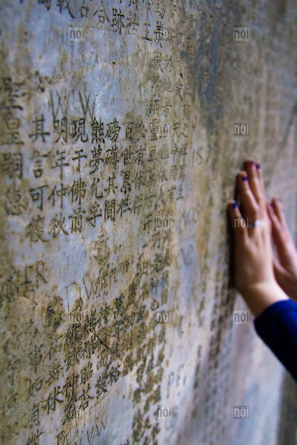 [photo by Francis Roux] Hands press up against a worn wall of Chua Thay on which Chinese scripting is carved, Hanoi outskirts, Vietnam