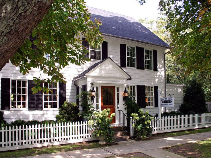White picket fence in The Hamptons, white house, black shutters, black roof
