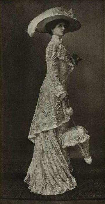 1909 - lady in walking suit and umbrella - looks as if she has a lorgnette in her left hand.