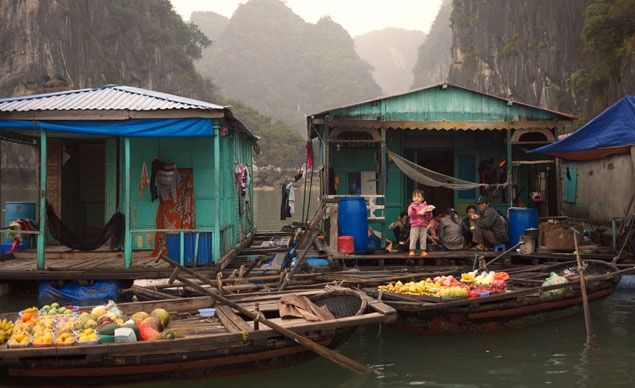 Set among the dramatic limestone cliffs of Vietnam's Ha Long Bay, the floating village of Cua Van is made up of a collection of docked boats and colorful raft houses.