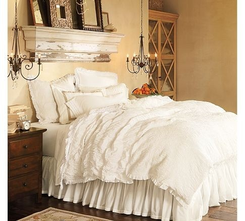 A fluffy white bed of coziness. Love the chandeliers on either side as well as the lovely distressed shelving above.