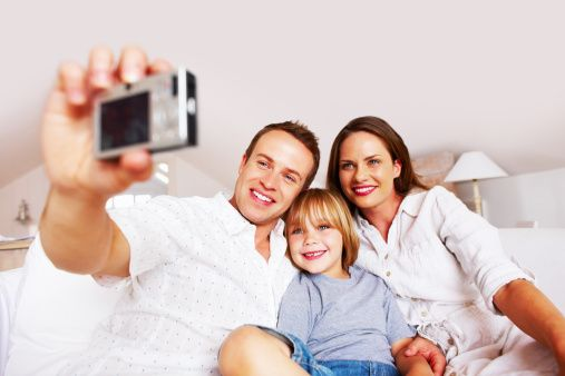Smiling middle aged man taking a photo of his family