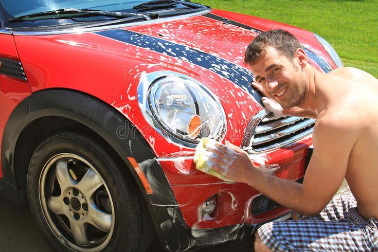 Car wash young man washing a car outdoors in the driveway