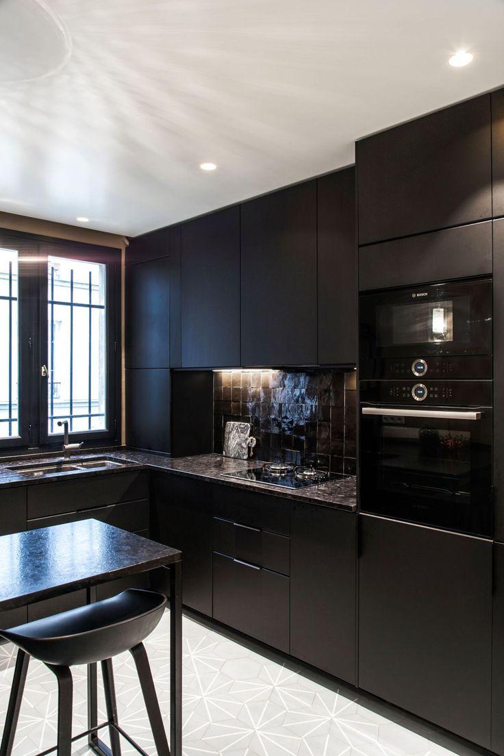 Dans la cuisine, la crédence marron et noire reprend la couleur du mur qui lui fait face