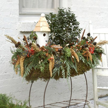 winter display with greenery and white birdhouse