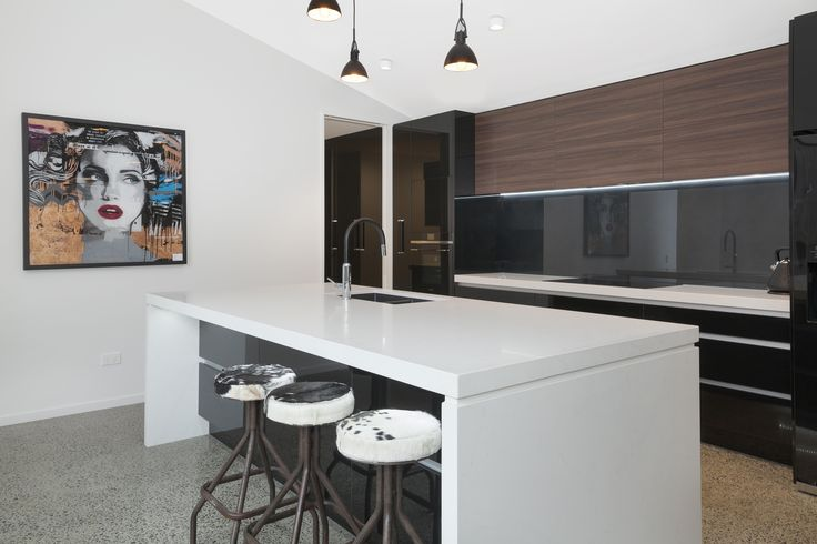 An entertainers kitchen features sleek black joinery.