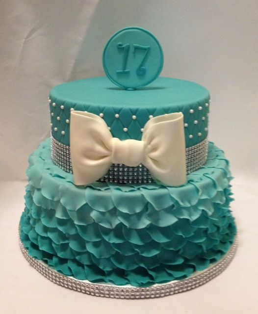 "Aqua Ombre Petal Cake - The design of this cake was specifically requested to mirror one from Fem Cakes. The bottom tier is a 10-inch with more than 200 ruffled petals in aqua with a subtle ombre effect. The top tier is an 8-inch with quilting and a gumpaste bow. I got the ""bling"" ribbon from Michael's and the 17 on top is on a circle of fondant with melted candy melts spread on the back to provide strength since I procrastinated in making it! Thanks for looking."