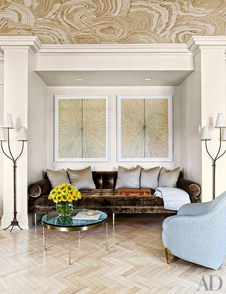 A living room alcove includes a pair of Mark Grotjahn works mounted over a custom-designed De Cárdenas daybed upholstered in a Bergamo fabric; the lamps are vintage Jean Royère, and the chair, covered in a Lelièvre jacquard, is by Garouste and Bonetti.