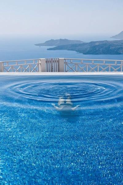 Immerse yourself in the refreshing waters of a stunning pool on the edge of caldera, at Petit Palace in Santorini