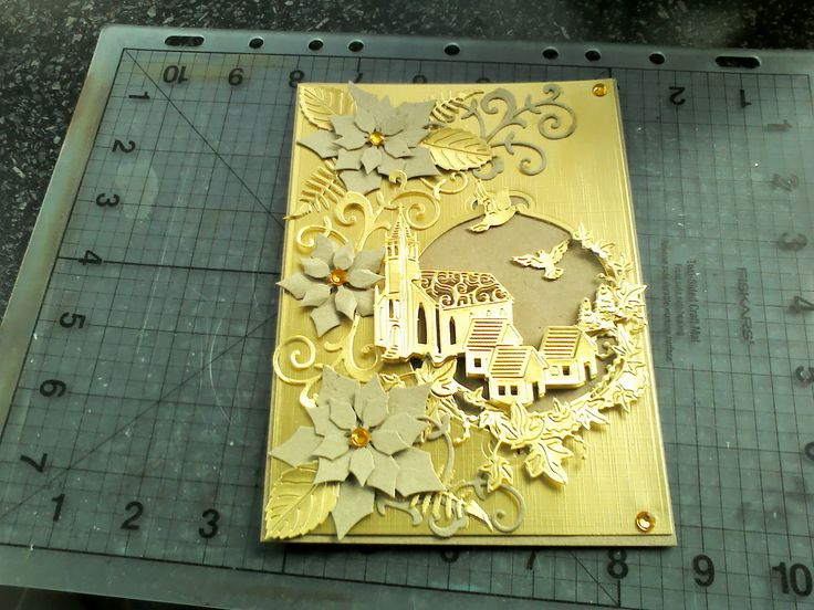 Made by Susan Balawajder - The very beautiful Tattered Lace Melded Village Church die cut into gold cardstock,the ivy and church cut again for extra depth backed with 3d foam.Spellbinders Layered Poinsettia in kraftcard,gold leaves from more Tattered Lace dies plus gems.