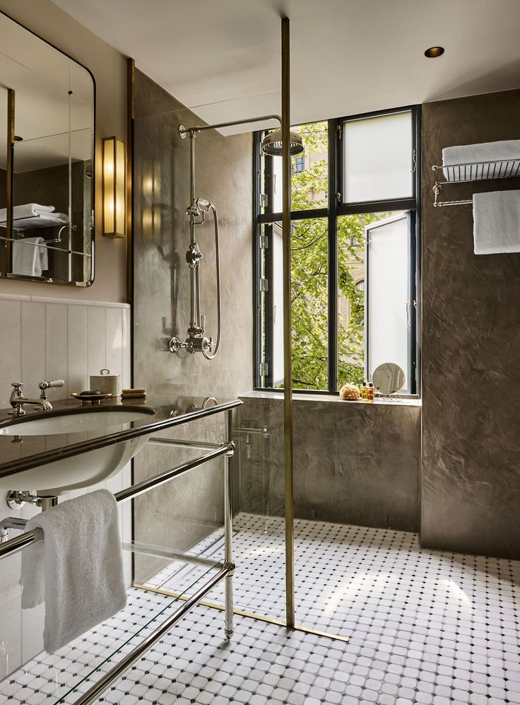 Stylish bathroom features a large walk-in shower and metallic accents in this boutique hotel in Copenhagen. [[MORE]] More pics and info