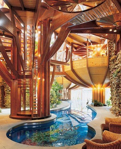 """A 75-foot-long pool winds its way along the lower level of the house. """"The owner wanted a lap pool running through a tropical garden with palm trees, banana trees and views of the sky,"""" the architect says..."""