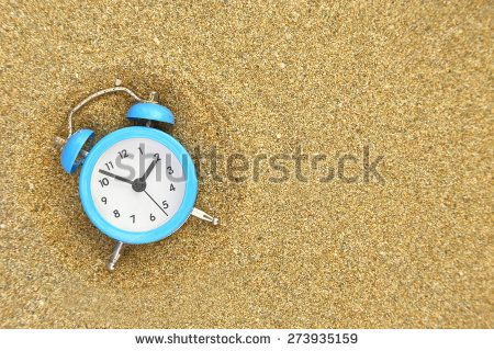 Vacation time. Alarm clock on the sand