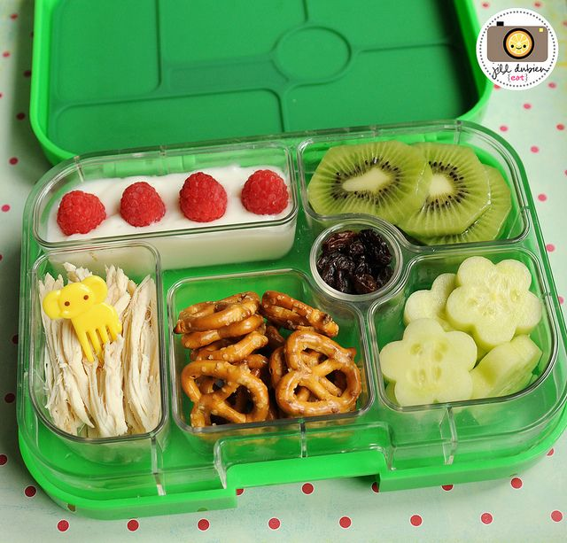 This Yumbox packed lunch features rotisserie chicken with a cute elephant pick, mini pretzel twists, flower-cut cucumbers, sliced kiwi, vanilla yogurt with fresh raspberries and raisins as a treat.