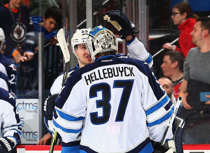 NEWARK, NJ - MARCH 28: Connor Hellebuyck #37 of the Winnipeg Jets is congratulated by Mark Scheifele #55 after defeating the New Jersey Devils in a shootout at Prudential Center on March 28, 2017 in Newark, New Jersey. (Photo by Andy Marlin/NHLI via Getty Images)