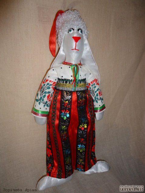 Заяц Казак – текстильная игрушка в украинском стиле. Размер: 38 см. Туловище – белый атлас, наполнитель – холлофайбер. Одежда – шаровары из красного атласа, ситцевая рубаха, казацкая шапка.