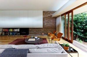 Eine nett aussehende ausgesetzt Ziegel Wand herausspringen aus der weißen Decke und weißen flachen getäfelten Schränke machen diese moderne Wohnzimmer mehr elegant. Foto von Downie Nord Architekten