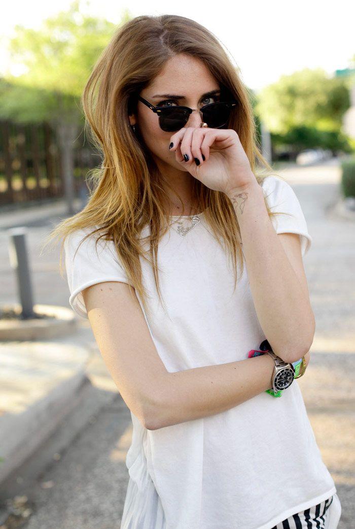 tatouage discret, cheveux lisses en blond foncé avec racines châtain, lunettes de soleil noires modèle femme