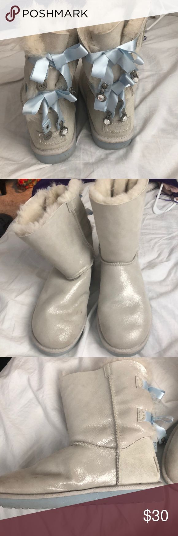 White Ugg boots Iridescent white Ugg boots. Limited Edition, worn a couple time. Slightly dirty but not noticeable. Blue ribbon back with jewels on ends. Bedazzled Ugg logo. One crystal missing on ribbon. UGG Shoes Winter & Rain Boots