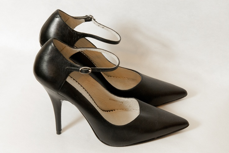 Black stilettos on thin heels with velcro at the ankle. Front of the cusp.