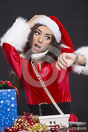 Desperate Santa girl speaking on the phone and checking the time on her wristwatch over dark background.