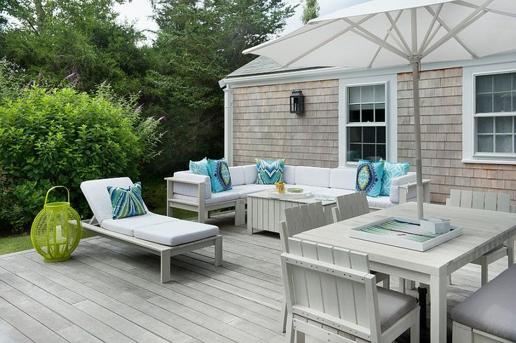 All-white outdoor decor for the deck with light blue accent pillows [Design: Annsley Interiors]