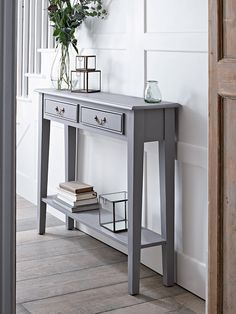 With a warm grey painted finish and two slender drawers with simple brass…