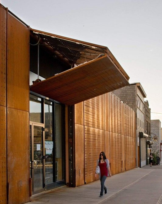 During the day the five motorized panels fold up to create awnings for the stores and to s...