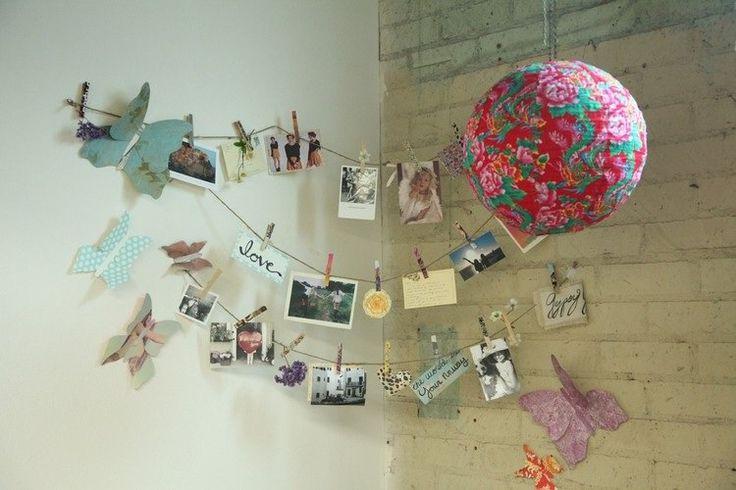 un coin désert dans la chambre de fille ado décoré de photos, papillons en papier et lanterne chinoise en papier
