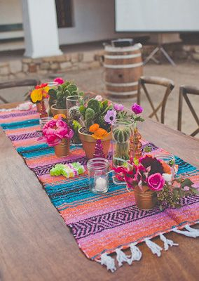 Mexican inspired dinner table with Mexican blanket used as a runner for patio