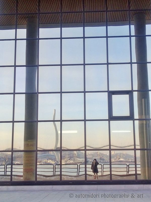 Can you see me there? The harbor and city of Vladivostok are reflected on the huge glass window wall.