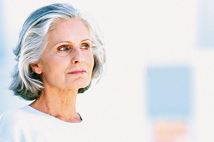 Mulher com cabelos brancos assumidos, em um corte chanel