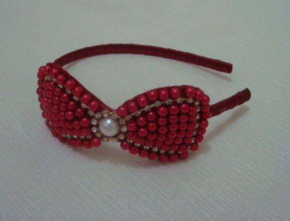 tiara encapada em fita cetim vermelha com laço em pérola vermelha e detalhes em strass, Pode ser confeccionada nas cores: branca, rosa e bege pérola. R$ 21,90