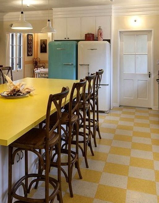 love how cheerful her kitchen looks with the side-by-side vintage (or at least vintage-looking) refrigerators and the yellow and white checkered floor.