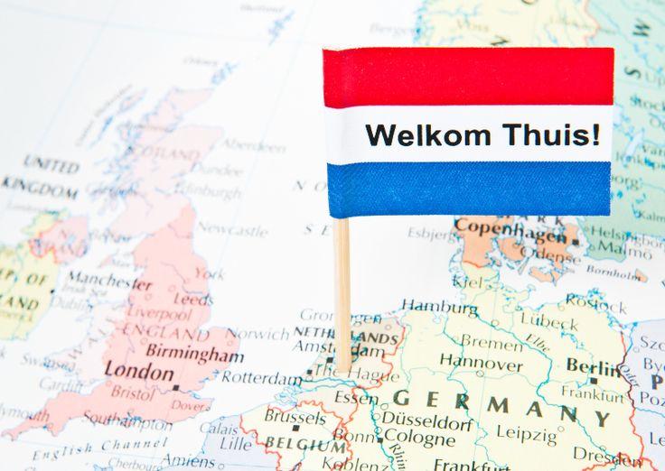 Een Nederlands vlaggetje met de tekst Welkom Thuis erop. De vlag is in een kaart van Europa geprikt, midden in Nederland. Leuk na  vakantie of reis!