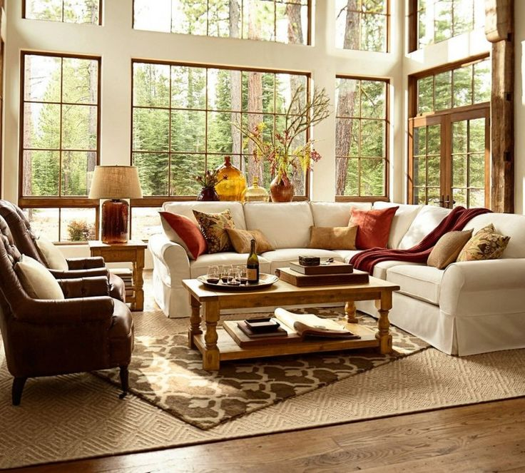 white soffa brown sofa chairs cream rug diagonal rug pillow throws white walls big glass window table lamp vases wooden deck floor of Pottery Barn:  The Best Pearce Sofa Maker