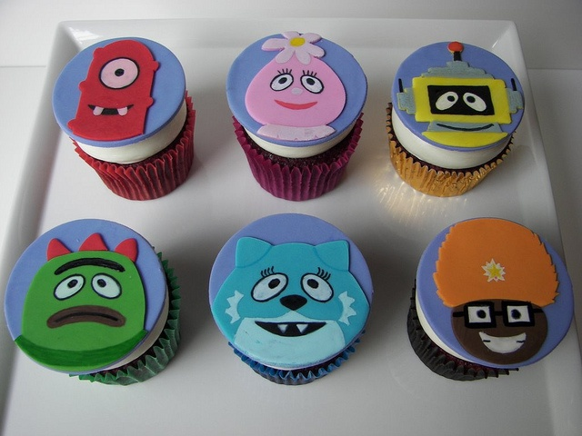 He asked for cupcakes instead of a cake and for a Yo Gabba Gabba theme. Thinking something along these lines with fondant character faces - maybe not such a large topper though?