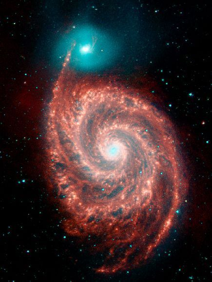 "This four-color view of the Whirlpool Galaxy was taken before Spitzer ran out of coolant. Combined with a visible-light photo taken by the Kitt Peak National Observatory, the picture highlights that the drastically different galaxies are merging. ""In visible light, that's not quite apparent. The infrared really shows it, though, as a red galaxy and a blue galaxy,"" Smith said, noting that studying such galaxy collisions was a primary goal of Spitzer."