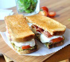 Répartissez uniformément de la sauce pesto sur 2 tranches de pain de mie.   Sur une des tranches, déposez 2 rondelles de tomate, 2 rondelles de mozzarella, une demi-tranche de jambon et un peu